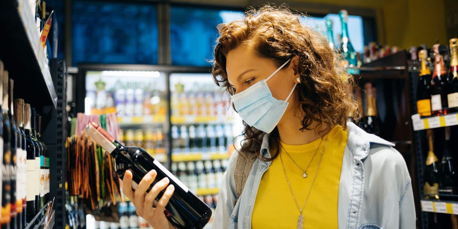 Young,Woman,Wearing,Protective,Face,Mask,Chooses,Wine,In,Grocery