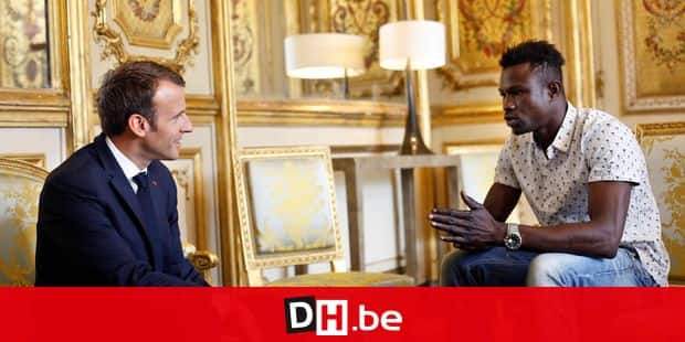 French President Emmanuel Macron (L) speaks with Mamoudou Gassama, 22, from Mali, at the presidential Elysee Palace in Paris, on May, 28, 2018. Mamoudou Gassama living illegally in France is being honored by Macron for scaling an apartment building over the weekend to save a 4-year-old child dangling from a fifth-floor balcony. The young Malian migrant who saved a four-year-old child hanging from a fourth-floor Paris balcony after scaling the facade with his bare hands will be made a French citizen, President Emmanuel Macron said. / AFP PHOTO / POOL / Thibault Camus