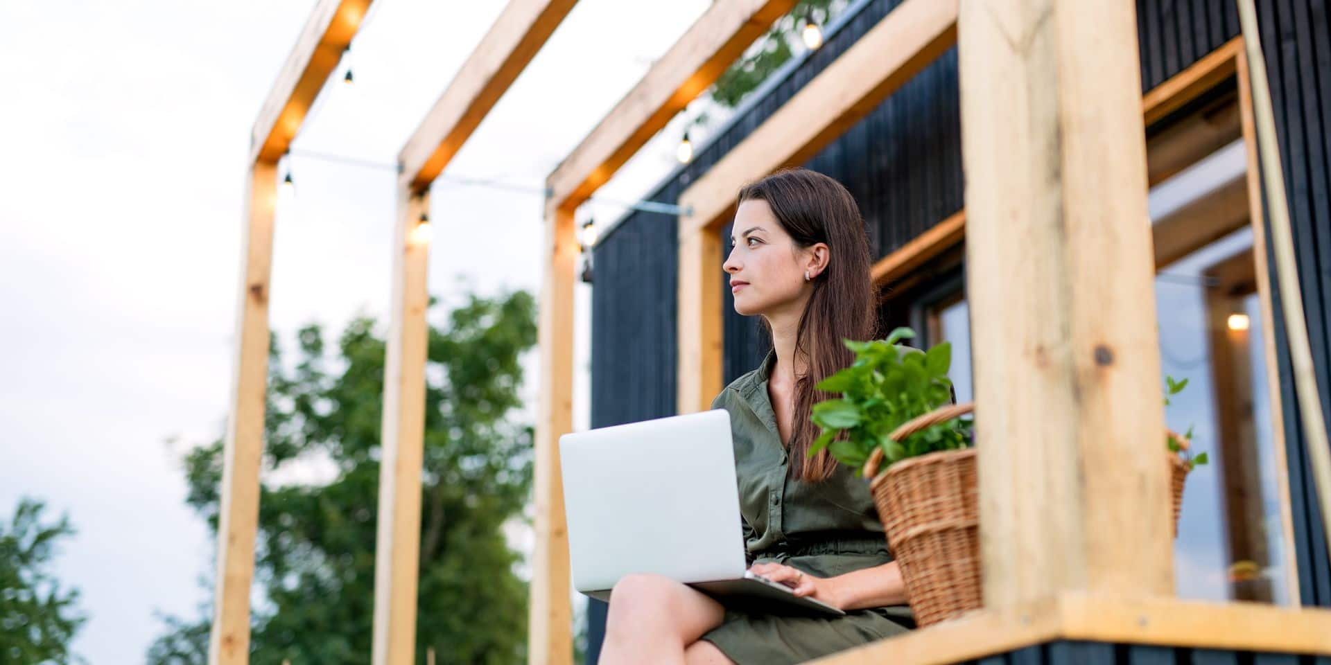 Young,Woman,With,Laptop,Outdoors,,Weekend,Away,In,Container,House
