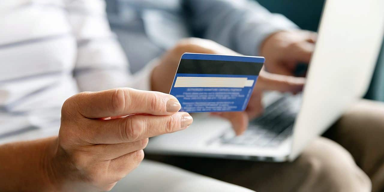 Close,Wife,Fingers,Holding,Plastic,Credit,Card,On,Background,Computer
