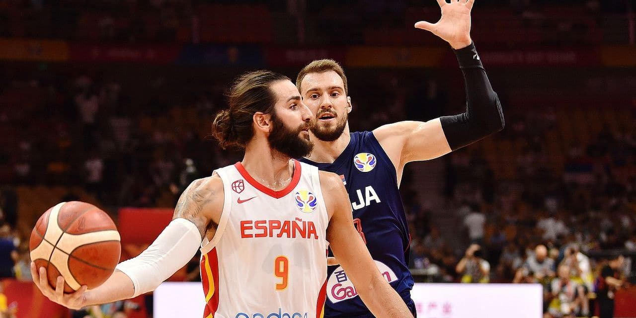 Spain's Ricky Rubio (L) passes the ball as Serbia's Marko Guduric tries to block during the Basketball World Cup Group J second round game between Spain and Serbia in Wuhan on September 8, 2019. (Photo by HECTOR RETAMAL / AFP)