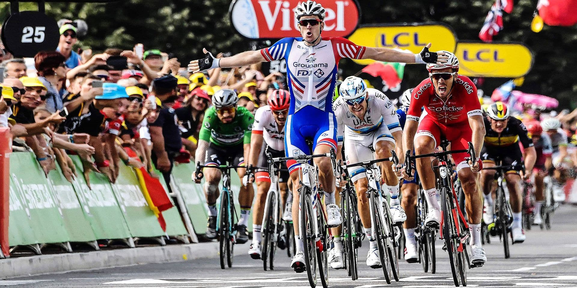 France's Arnaud Demare (C) celebrates as he crosses the finish line to win, ahead of France's Christophe Laporte (R) the 18th stage of the 105th edition of the Tour de France cycling race, on July 26, 2018 between Trie-sur-Baise and Pau, southwestern France. / AFP PHOTO / Jeff PACHOUD